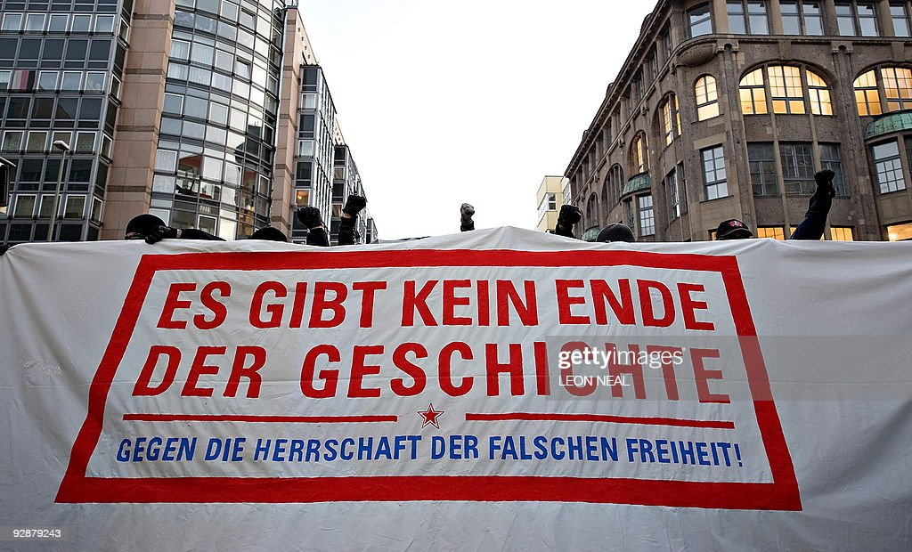 A protestor raises a fist from behind a banner which reads 'There is no end to history' during a demonstration by Leftist groups in central Berlin on...