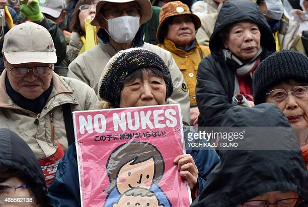A protestor raises an anti nuclear placard at a rally denouncing nuclear power plants in Tokyo on March 8 2015 Thousands of people took part in the...