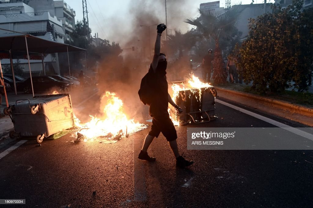 A protestor raises his fist as antifascist demonstrators clash with riot police in Athens on September 18 after a leftist musician was murdered by a...