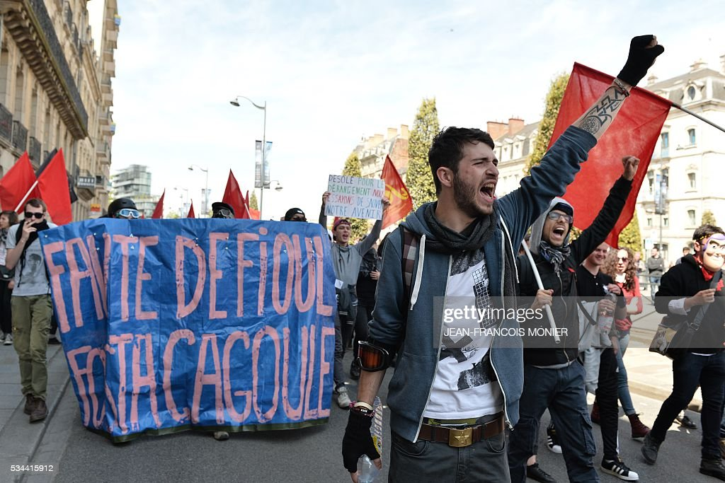 A protestor raises his fist during a protest against the government's labour market reforms in Rennes, northwestern France, on May 26, 2016. The French government's labour market proposals, which are designed to make it easier for companies to hire and fire, have sparked a series of nationwide protests and strikes over the past three months.
