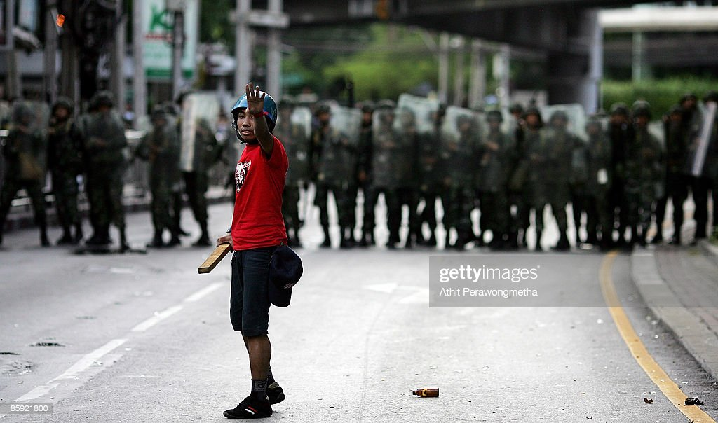 A protestor reacts in front of soldiers during a protest near Victory Monument on April 13, 2009 in Bangkok, Thailand. Prime Minister Abhisit has called for calm as clashes between the Thai army and anti government protestors have escalated, resulting in reports of the army having fired live rounds over the heads and into crowds of demonstrators.