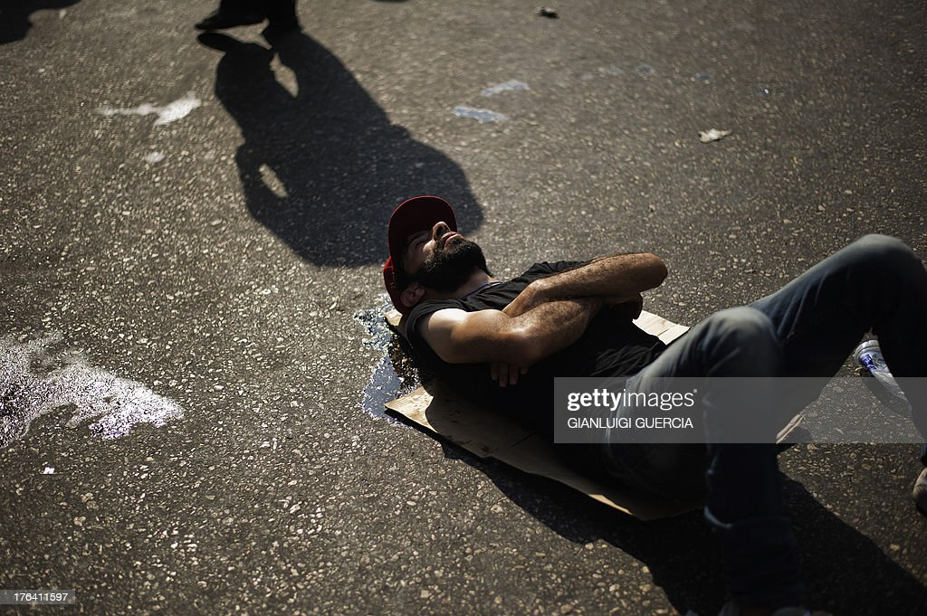 A protestor rests on the ground as members of the Muslim Brotherhood and supporters of Egypt's ousted president Mohammed Morsi demonstrate outside the High Court in Cairo on August 12, 2013. Egypt's judiciary said it was extending Morsi's detention for a further 15 days pending an investigation into his collaboration with Hamas, which rules neighbouring Gaza.