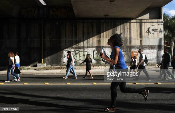 A protestor runs as others march following the funeral of Vanessa dos Santos who was shot in the head and killed in the doorway of her house during a...