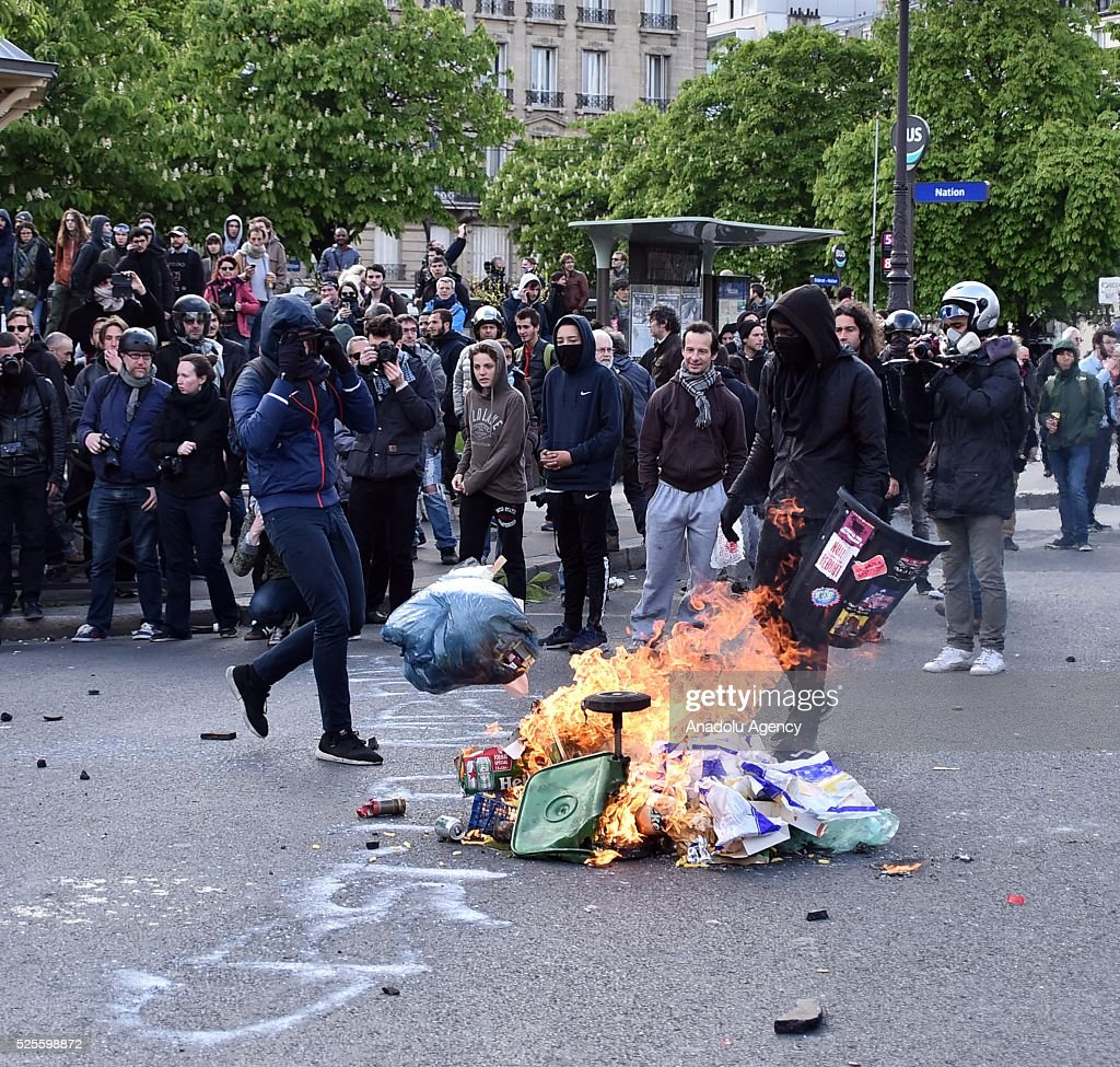 A protestor set garbage cans on fire during a protest against the French government's proposed labour reforms at the Place de la Nation in Paris, France on April 28, 2016. Protesters clashed with police in Paris and western France on April 28 as workers and students across the country made a new push for the withdrawal of a hotly contested labour bill.