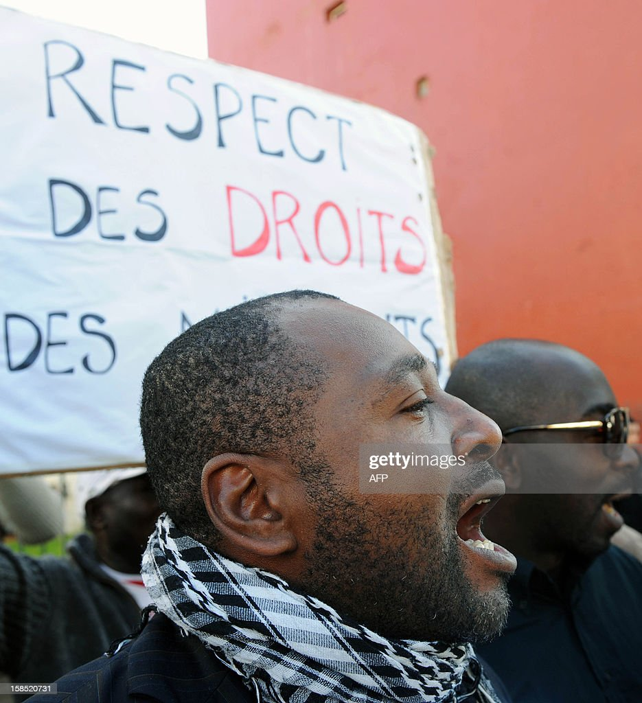A protestor shouts slogans outside a court in Rabat on December 18, 2012, during a demonstration against the trial of Camara Laye, the founder of the Council of Sub-Saharan migrant in Morocco (CMSM), who was tried for illegally selling alcohol and cigarettes. According to the police, Camara was arrested in the night of October 20 to October 21, 2012 at his home where police found three bottles of wine and two cartons of cigarettes. PHOTOS