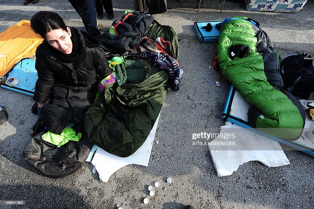 A protestor sits in front of the main building of the state public television in Budapest on December 20, 2012. A group of protestors who have been demonstrating for over a year outside the Budapest headquarters of Hungary's state-run public media said that security guards had pulled down their camp. The protesters have held their camp for 374 days to protest what they see as distorted information in the state-run media. AFP PHOTO / ATTILA KISBENEDEK