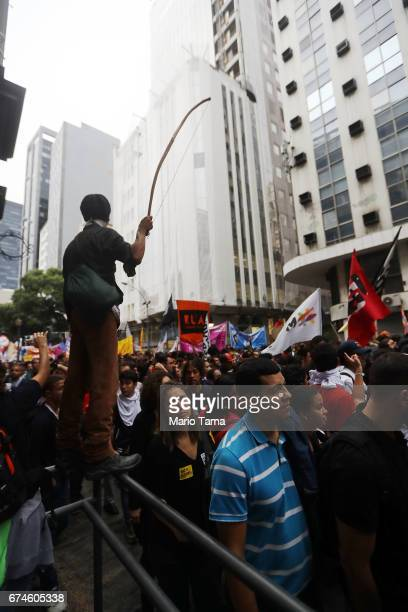 A protestor stands holding a bow at demonstrations during a nationwide general strike on April 28 2017 in Rio de Janeiro Brazil The general strike...