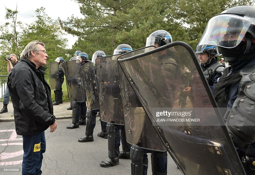 A protestor stands in front of French riot police officers during a protest against the government's labour market reforms in Rennes, northwestern France, on May 26, 2016. The French government's labour market proposals, which are designed to make it easier for companies to hire and fire, have sparked a series of nationwide protests and strikes over the past three months.