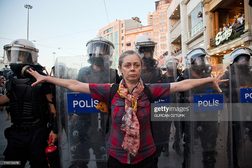 A protestor stands in front of Turkish police during a demonstration near the entrance of Taksim Square on July 20, 2013, in Istanbul. Baton-wielding police broke up a crowd of around a thousand fellow activists who had turned up for the wedding of Nuray Cokol, a 32-year-old nurse, and Ozgur Kaya, a 34-year-old electrician, in Gezi Park. Nuray and Ozgur fell in love behind the barricades of last month's mass anti-government protests in Istanbul and picked the epicentre of the revolt on Taksim Square as the venue to tie the knot on July 20.