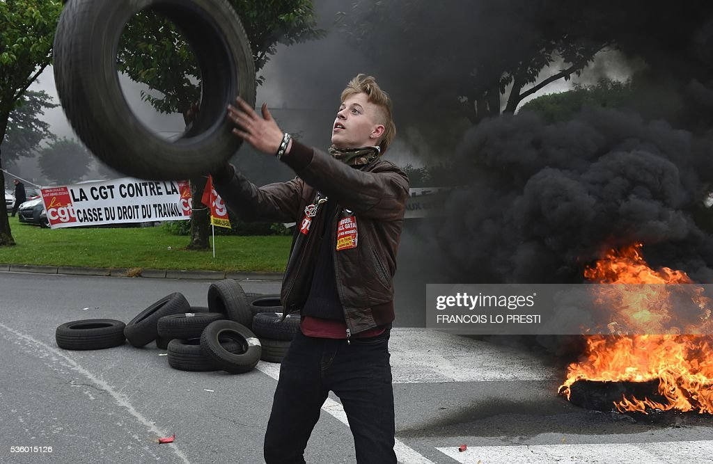A protestor stands next to tires on fire and a French CGT union's banner at the Simmons factory in Saint Amand les Eaux, northern France on May 31, 2016 during a visit of the French Economy Minister after a meeting on reindustrialisation in the North of France. / AFP / FRANCOIS