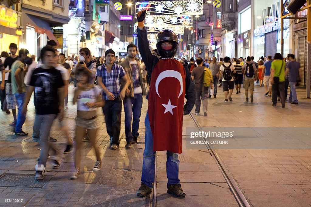 A protestor stands with a Turkish flag on July 14, 2013 on Istiklal Avenue in the center of Istanbul. Turkish riot police fired rubber bullets, tear gas and water cannon to disperse hundreds of protesters trying to enter an Istanbul square that was the cradle of deadly unrest that engulfed the country in June. The police moved in when demonstrators protesting in the city's Beyoglu neighborhood against Prime Minister Recep Tayyip Erdogan moved toward nearby Taksim Square.