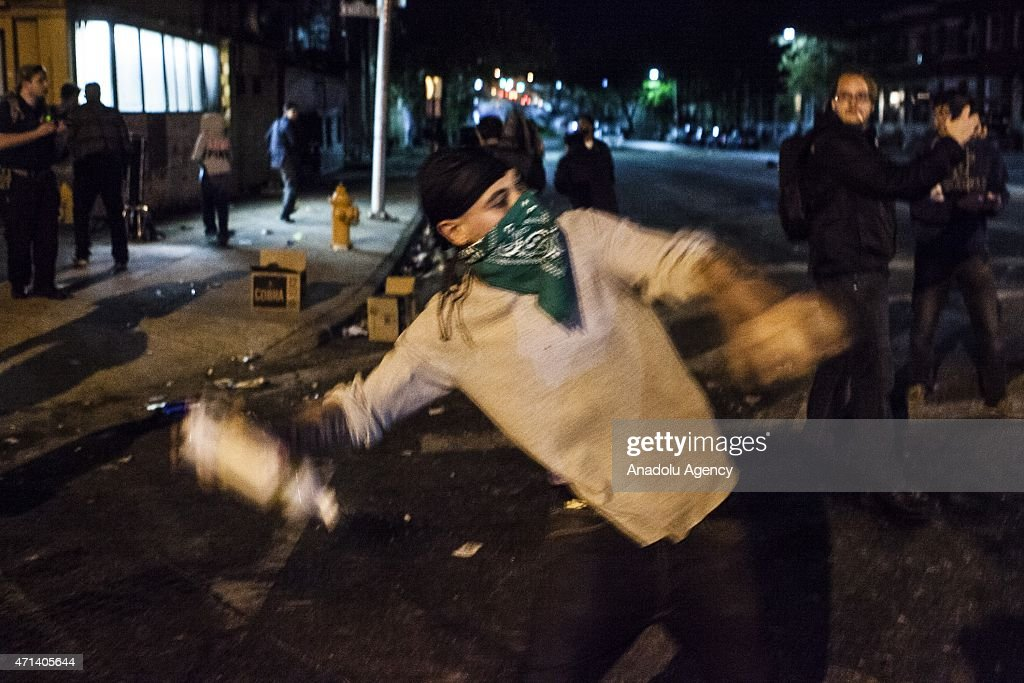 A protestor throws a liquor bottle at police lines during riots in Baltimore USA on April 27 2015 Protests following the death of Freddie Gray from...