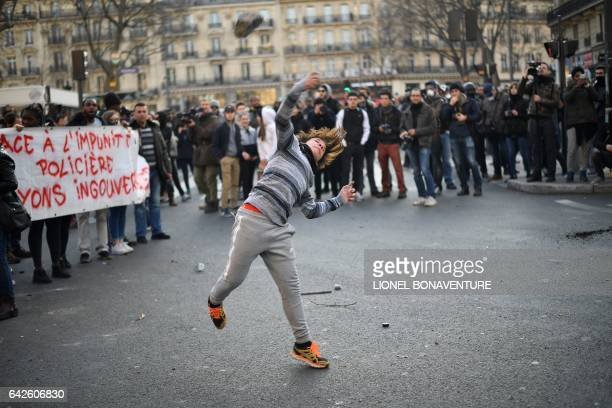 A protestor throws a stone during a demonstration against police brutality on February 18 2017 on the place de la Republique in Paris following the...