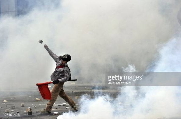 A protestor throws a stone to police near the Parliament building in the center of Athens on May 5 2010 A nationwide general strike gripped Greece in...