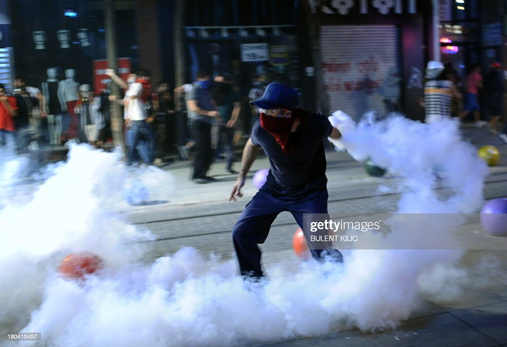 A protestor throws back a gas canister on September 12, 2013 at Kadikoy in Istanbul. Thousands of people angry over the death of a 22-year-old demonstrator in southern Turkey on Monday clashed with police in Istanbul, the capital Ankara, the western city of Izmir as well as in the southern cities of Mersin and Atakya.