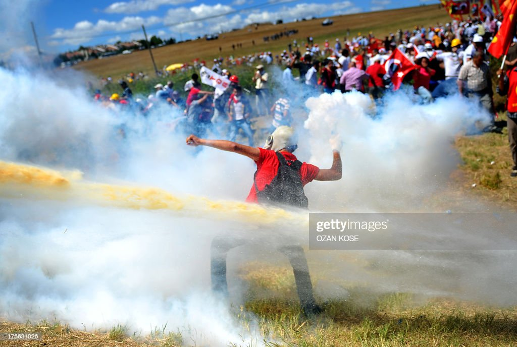 A protestor throws back a tear gas canister during clashes with police and gendarmes blocking the access to a courthouse in Silivri near Istanbul on...