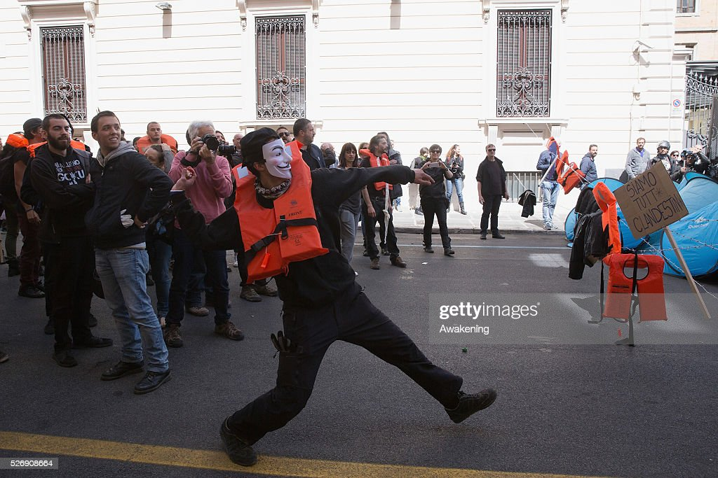 A protestor throws eggs to the police during May Day protests on May 01, 2016 in Rome, Italy. Police clashed with protestors as hundreds took to the streets to participate in May Day marches and gatherings across Italy, with many demonstrators protest against Erdogan decisions about the migrant crisis.