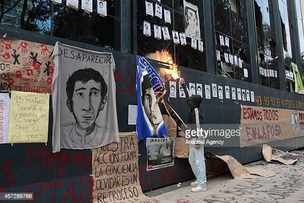 A protestor tries to set fire to the placard outside the Attorney General's Office in Mexico City Mexico on October 15 2014 during a protest over the...
