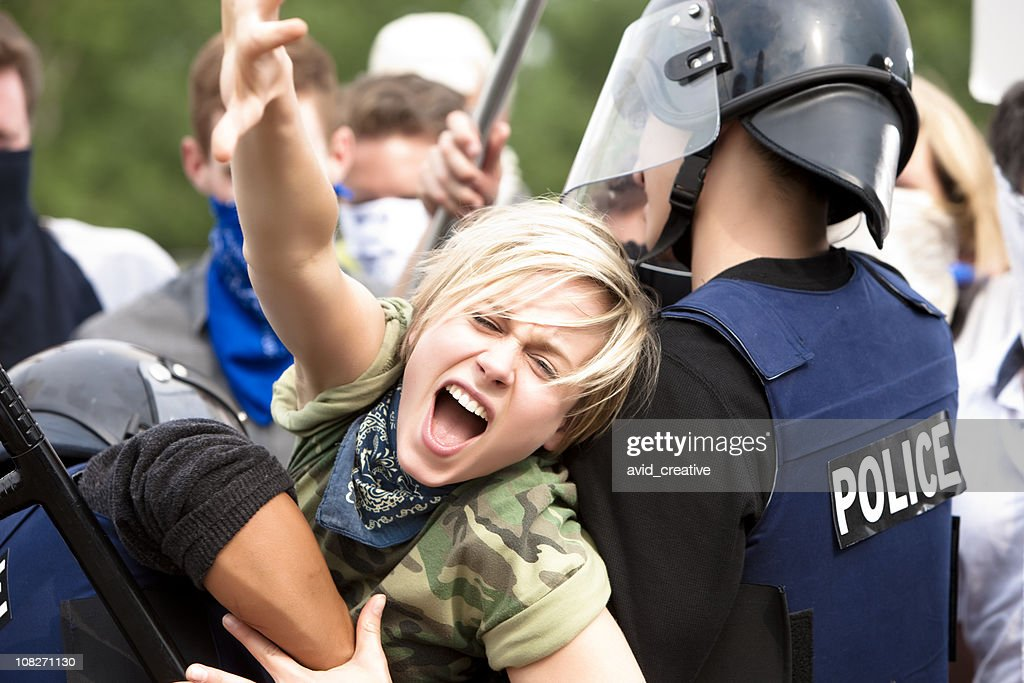 Protestor Trying to Get Through Police Barricade : Stock Photo