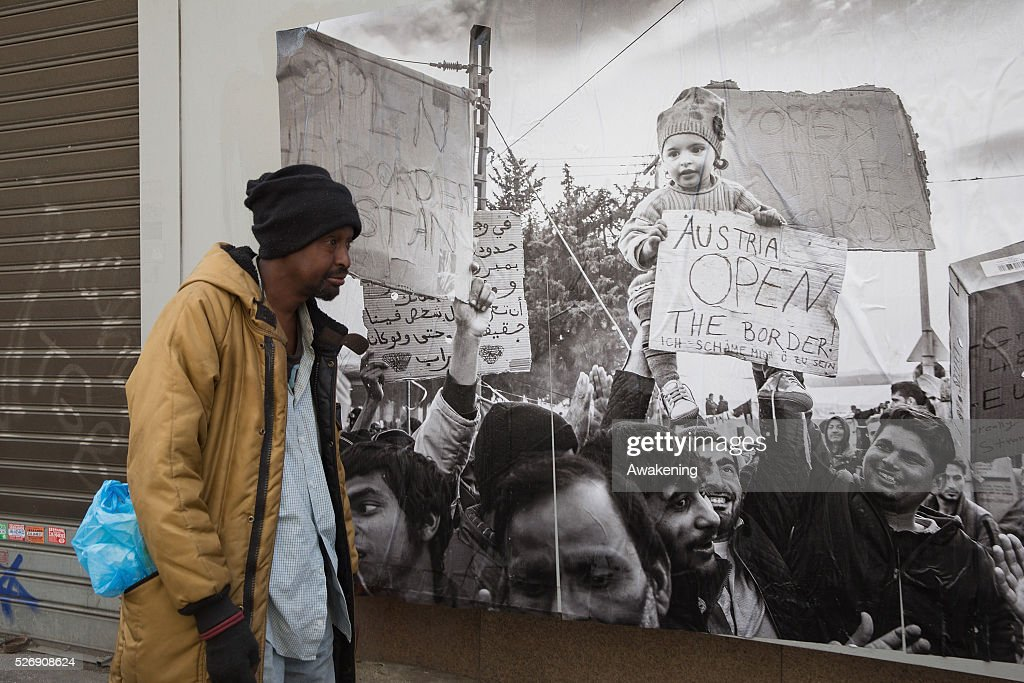A protestor walks in front of a poster during May Day protests on May 01, 2016 in Rome, Italy. Police clashed with protestors as hundreds took to the streets to participate in May Day marches and gatherings across Italy, with many demonstrators demanding a solution to the migrant crisis.