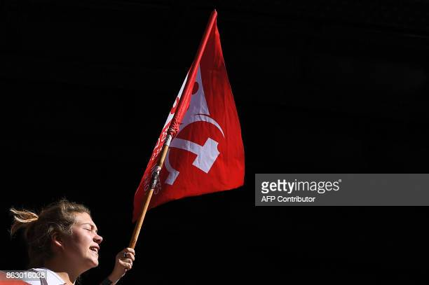 A protestor walks near a flag as she takes part in a demonstration called by the General Confederation of Labour French worker's union in Marseille...