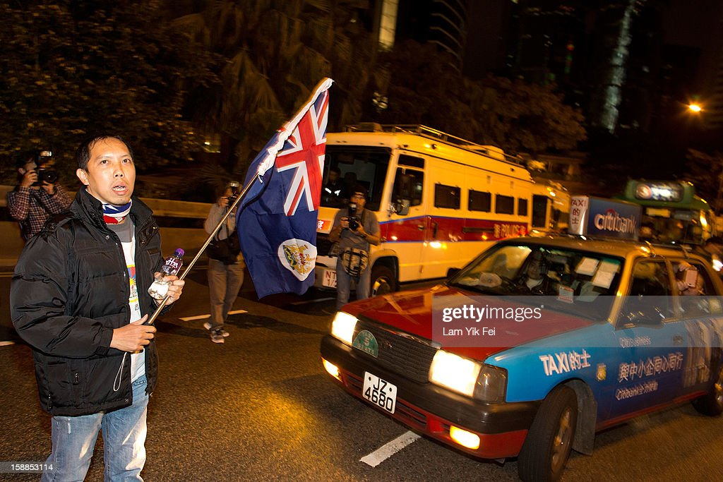 A protestor waves a colonial Hong Kong flag as he blocks the traffic, during a protest against embattled Hong Kong Chief Executive Leung Chun-ying, on January 1, 2013 in Hong Kong, Hong Kong. According reports, tens of thousands of protestors took to the streets demanding greater democracy 15 years after returning to Chinese rule.