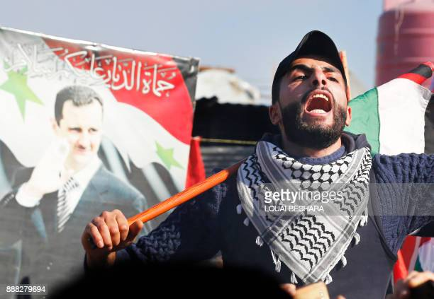 A protestor waves the Palestinian flag next to a poster of the Syrian president during a demonstration against US President Donald Trump's decision...