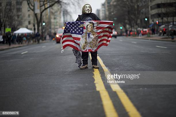 A protestor wearing a Guy Fawkes mask demonstrates in the street after the inauguration of Donald Trump as the 45th President of the United States...