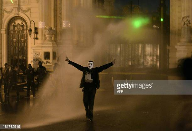 A protestor wearing a Guy Fawkes mask trademark of the anonymous movement and based on a character in the film V for Vendetta is sprayed by water as...