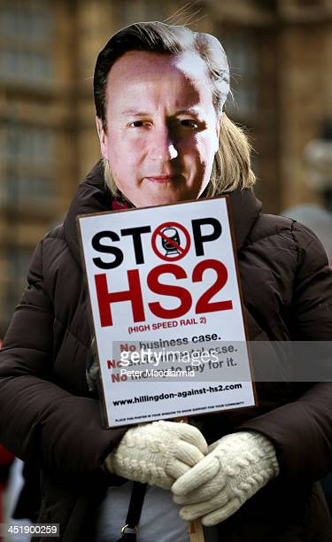 A protestor wearing a mask depicting Prime Minister David Cameron demonstrates against the High Speed 2 rail line at Parliament on November 25 2013...