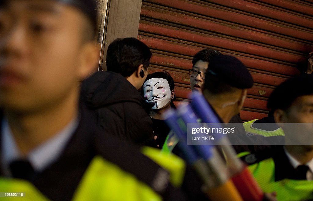 A protestor, wearing an 'anonymous mask', is arrested by police, during a protest against embattled Hong Kong Chief Executive Leung Chun-ying, on January 1, 2013 in Hong Kong, Hong Kong. According reports, tens of thousands of protestors took to the streets demanding greater democracy 15 years after returning to Chinese rule.