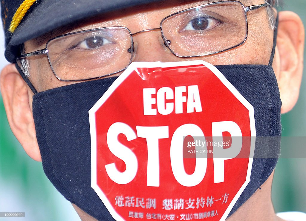 A protestor wears a facemask attached with an 'anti-ECFA' sign during a sit-in protest in Taipei on May 20, 2010. Hundreds of supporters of Taiwan's major pro-independence opposition rallied in the capital city as part of the party's efforts to stop the government from forging a trade pact with China. ECFA stands for Economic Cooperation Framework Agreement, a contentious trade pact Taiwanese government plans to sign to sign with China.