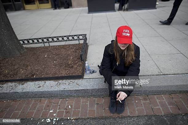 A protestor wears a 'Fuck Trump' hat while smoking a cigarette after the inauguration of Donald Trump as the 45th President of the United States...