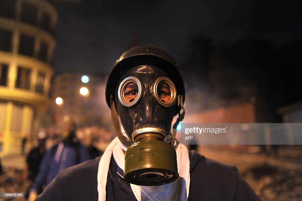 A protestor wears a gas mask during clashes near Taksim Square in Istanbul on June 4, 2013, as part of ongoing protests against the ruling party, police brutality, and the destruction of Taksim park for a development project. Turkey's Islamic-rooted government apologised today to wounded protestors and said it had 'learnt its lesson' after days of mass street demonstrations that have posed the biggest challenge to Prime Minister Recep Tayyip Erdogan's decade in office. Turkish police had on June 1 begun pulling out of Istanbul's iconic Taksim Square, after a second day of violent clashes between protesters and police over a controversial development project. What started as an outcry against a local development project has snowballed into widespread anger against what critics say is the government's increasingly conservative and authoritarian agenda. AFP PHOTO/OZAN KOSE