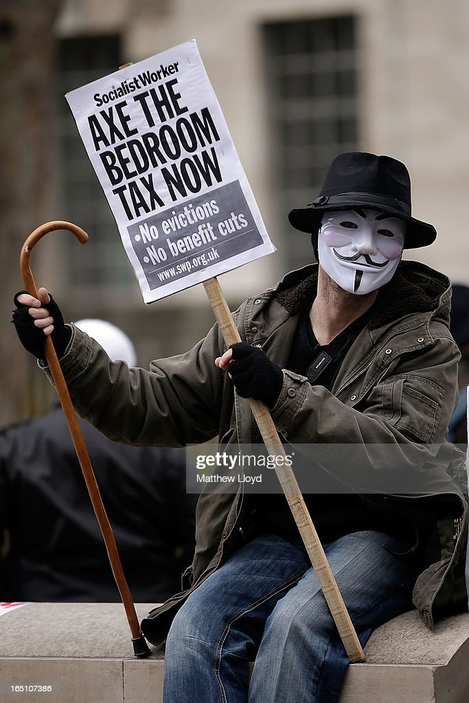 A protestor wears a mask holding a cane and sign while demonstrating against the proposed 'bedroom tax' gather in Trafalgar Square before marching to Downing Street on March 30, 2013 in London, England. Welfare groups are protesting the government's plans to cut benefits where families have surpassed the number of rooms they require.