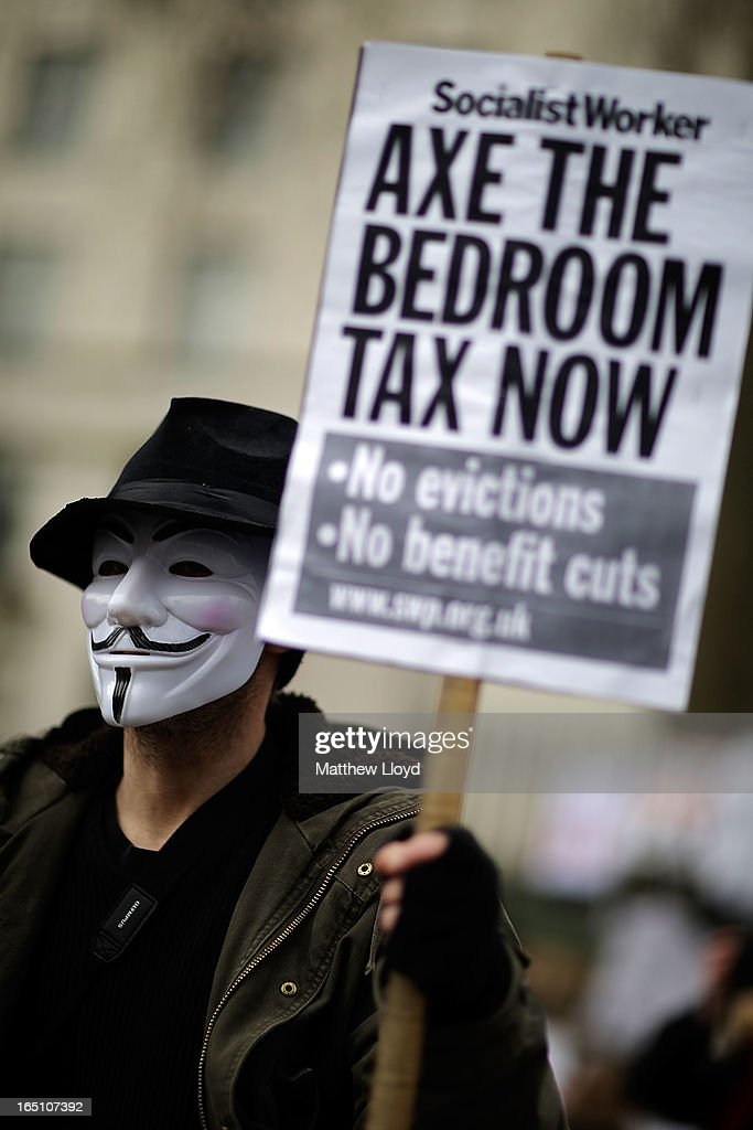 A protestor wears a mask holding a sign while demonstrating against the proposed 'bedroom tax' gather in Trafalgar Square before marching to Downing Street on March 30, 2013 in London, England. Welfare groups are protesting the government's plans to cut benefits where families have surpassed the number of rooms they require.