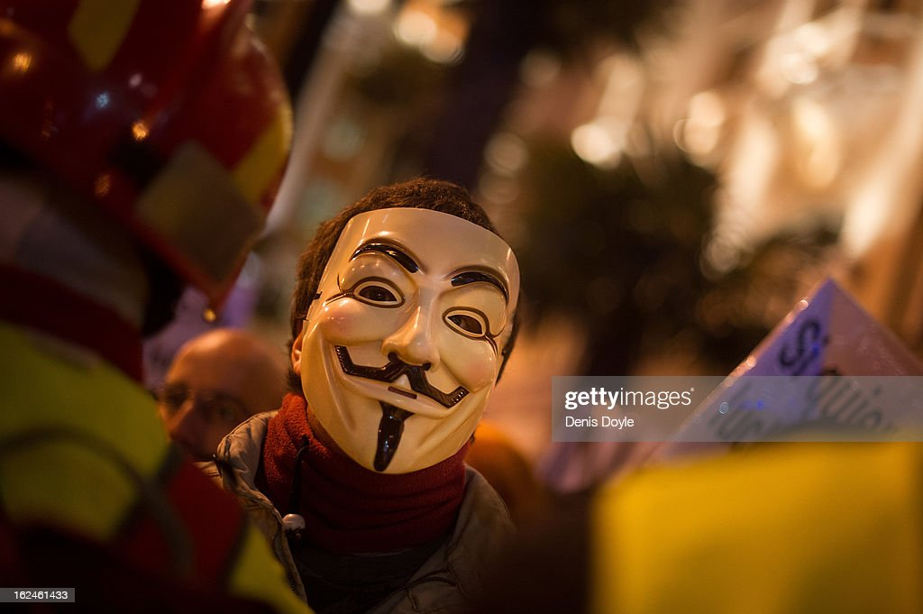 A protestor wears a mask of 'Anonymous' the loosely associated hacking group during a march by thousands of people on February 23, 2013 in Madrid, Spain. Public health workers, civil servants and disaffected citizens converged on central Madrid to protest against the austerity measures of Prime Minister Mariano Rajoy.