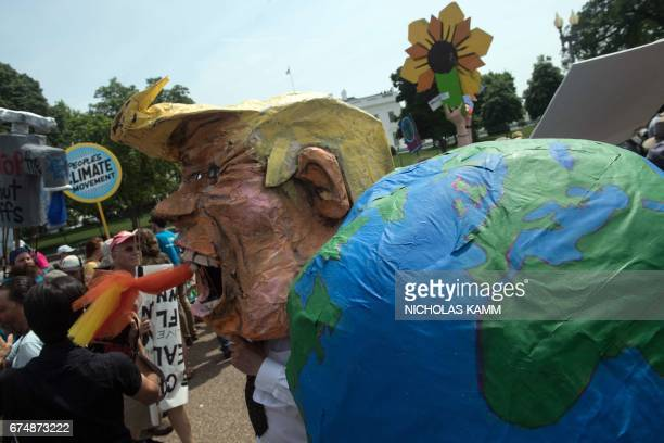 TOPSHOT A protestor wears a mask of US President Donald Trump in front of the White House during the People's Climate March in Washington DC on April...