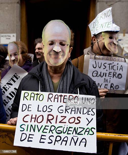 A protestor wears a mask representing Rodrigo Rato and holds a sign during a demonstration against Rodrigo Rato former chairman of Spanish bank...