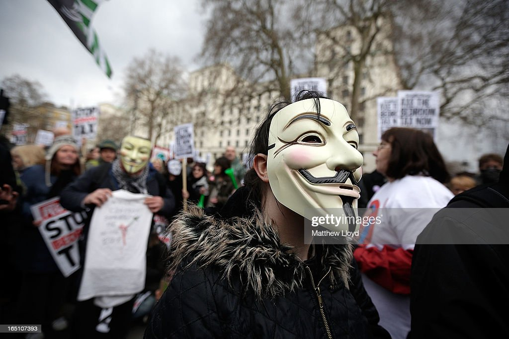A protestor wears a mask while demonstrating against the proposed 'bedroom tax' gather in Trafalgar Square before marching to Downing Street on March 30, 2013 in London, England. Welfare groups are protesting the government's plans to cut benefits where families have surpassed the number of rooms they require.