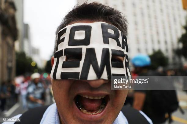A protestor wears a mask written in Portuguese which means 'Temer Get Out' while marching at demonstrations during a nationwide general strike on...