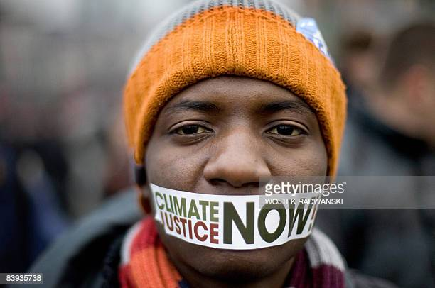 A protestor wears a sticker on his mouth reading 'Climate Justice Now' in front of a demonstration against climate change in central Poznan during...