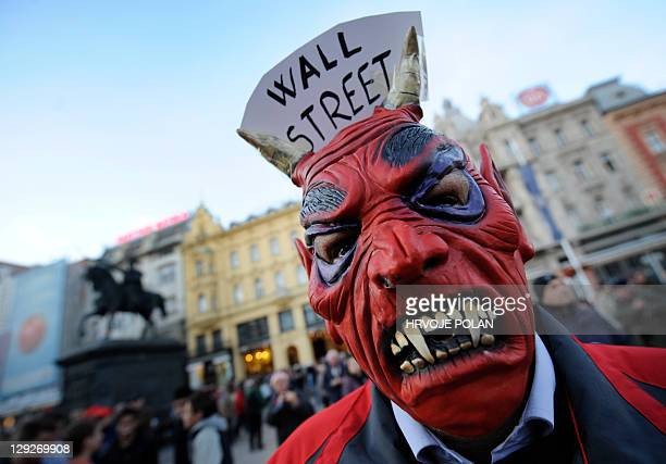 A protestor wears a vampire mask with 'Wall Street' sign on October 15 2011 during a demonstrations in Zagreb Some 3000 demonstrators gathered on...