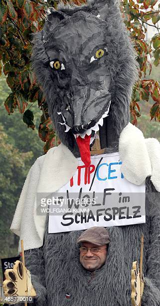 A protestor wears a wolf costume with a sign reading ' TTIP/CETA=Wolf in sheep's clothing' during a demonstration against the Transatlantic Trade and...