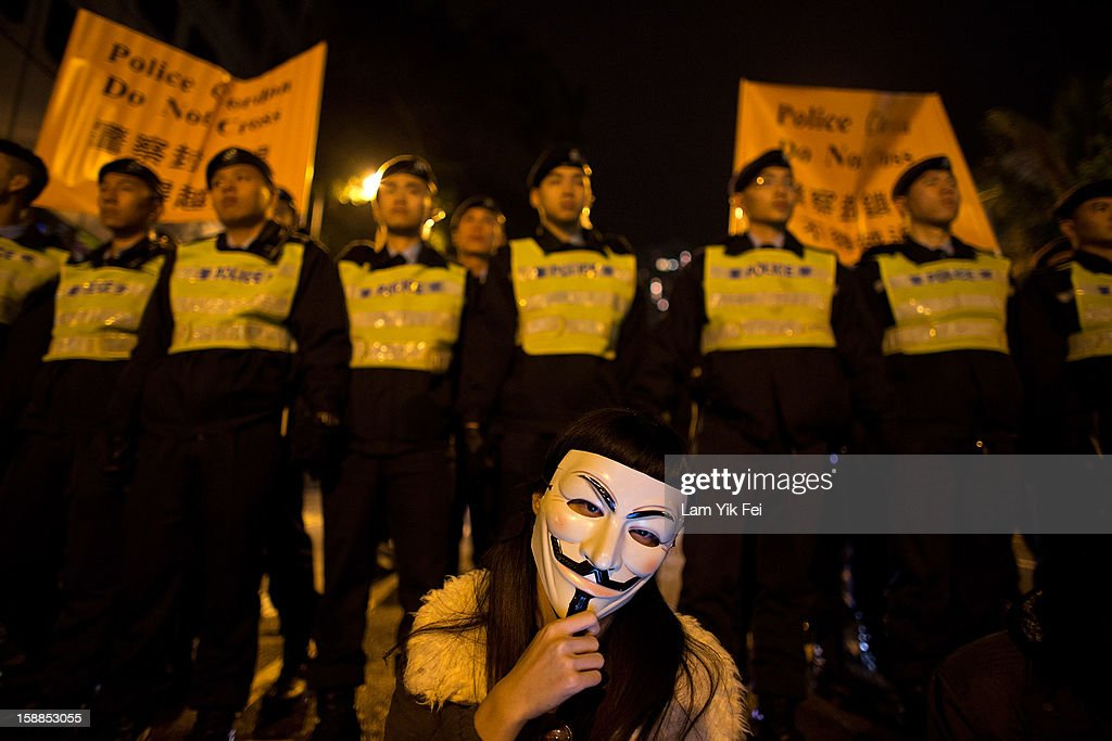 A protestor wears an 'anonymous mask' in front of police who link arms to prevent protestors from reaching the front gate of government house, during a protest against embattled Hong Kong Chief Executive Leung Chun-ying, on January 1, 2013 in Hong Kong, Hong Kong. According reports, tens of thousands of protestors took to the streets demanding greater democracy 15 years after returning to Chinese rule.