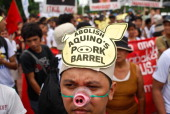 A protestor wears an anti 'pork barrel' head gear and a pig snoutwith a pig snout during a protest against the misuse of Philippine state funds...
