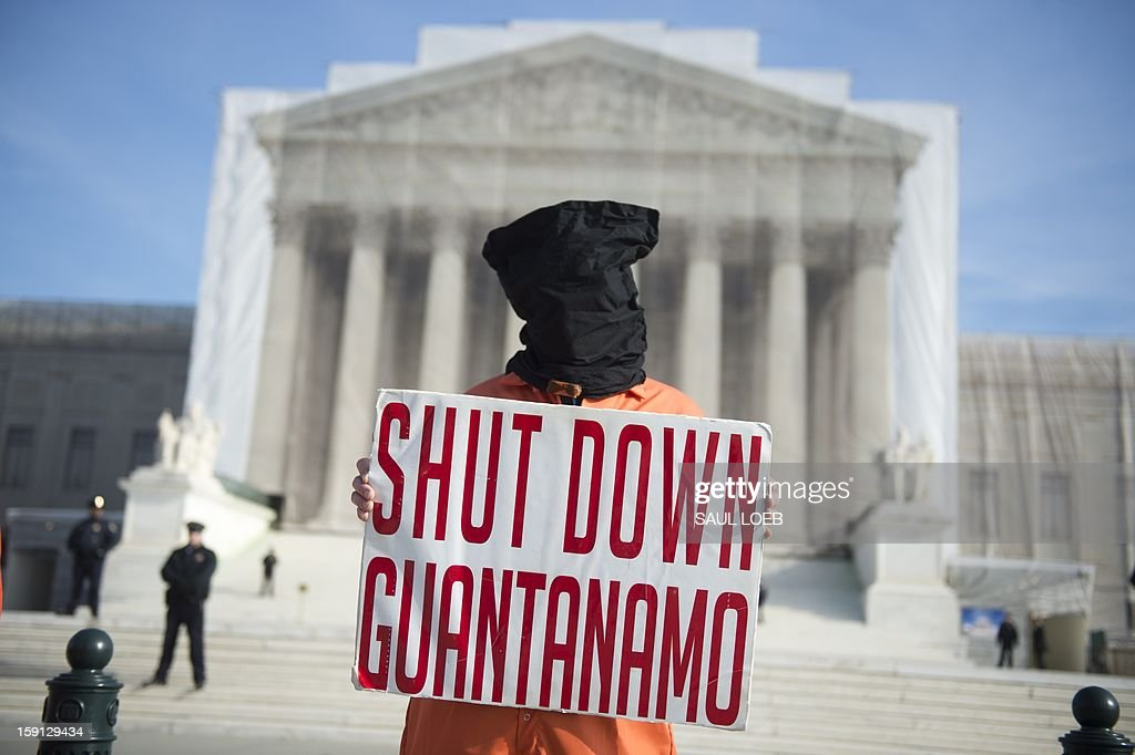 A protestor wears an orange prison jump suit and black hood on their head during protests against holding detainees at the military prison in Guantanamo Bay during a demonstration in front of the US Supreme Court in Washington, DC, on January 8, 2013. This weeks marks the 11th anniversary of the opening of the prison. AFP PHOTO / Saul LOEB
