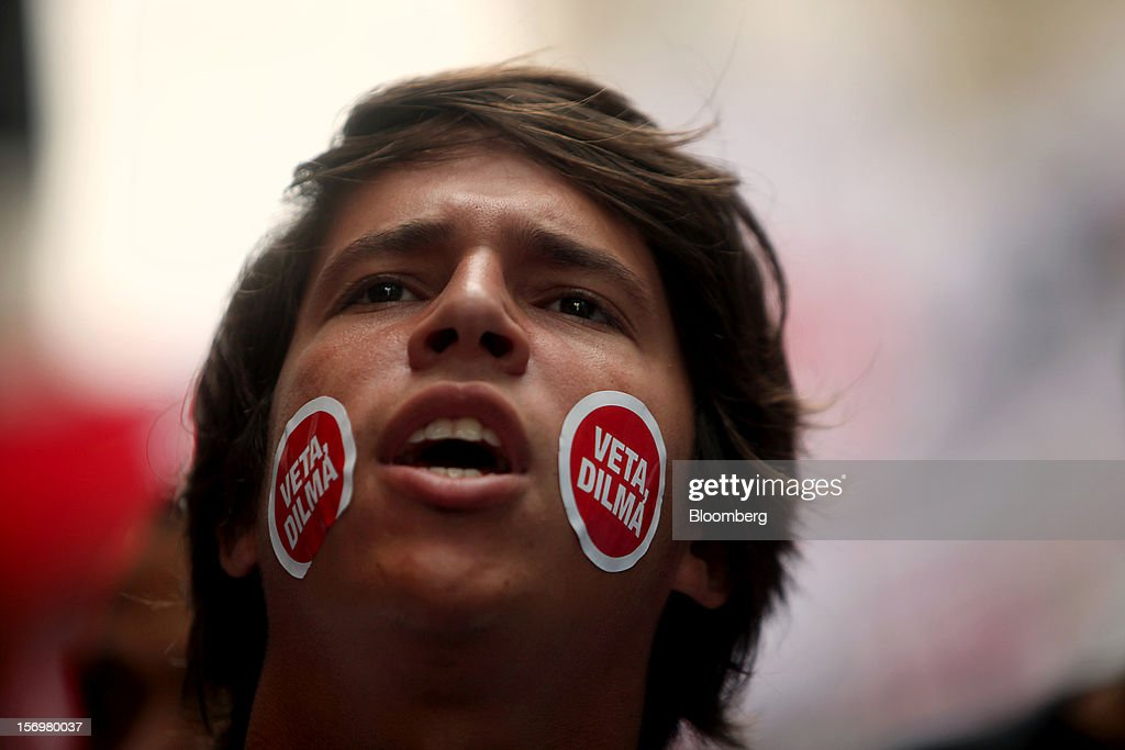 A protestor wears 'Veta, Dilma' stickers on his face during a demonstration in Rio de Janeiro, Brazil, on Monday, Nov. 26, 2012. Tens of thousands of residents in Rio de Janeiro attended a rally today urging Brazilian President Dilma Rousseff to veto an oil royalties law that the state's governor claimed will derail the 2016 Olympics. Photographer: Dado Galdieri/Bloomberg via Getty Images