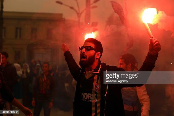 A protestor who calls himself as 'anticoup protestor' hold flares outside the Cairo University on the anniversary of former Egyptian President Hosni...