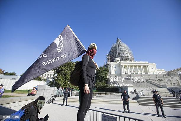 A protestor with a flag stands on a barrier in front of the US Capitol during the Anonymous Million Mask March around the world in Washington USA on...